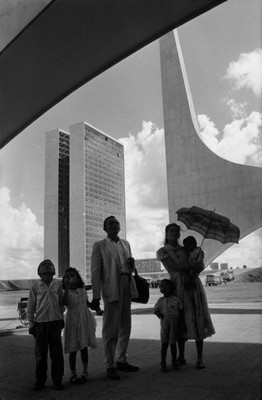 A worker from Nordeste shows his family the new city on inauguration day. In the background: the National Congress building by Oscar Niemeyer. Brasilia, Brazil, 1960 © René Burri / Magnum Photos