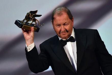Le réalisateur suédois Roy Andersson tient le Lion d'or lors de la cérémonie de clôture de la 71e Mostra de Venise, samedi 6 septembre 2014. | GABRIEL BOUYS/AFP