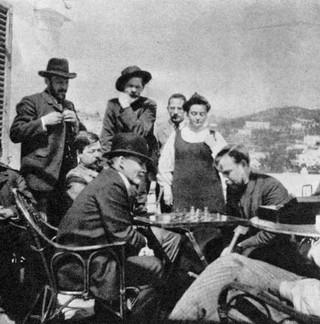 Lenin mentre gioca a scacchi con Bogdanov sulla terrazza di casa Gorkij a Capri nell'aprile del 1908. Sullo sfondo Gorkij che li guarda.